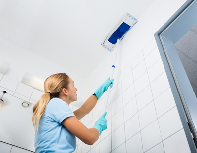 Ceiling being swept by cleaning lady in bathroom