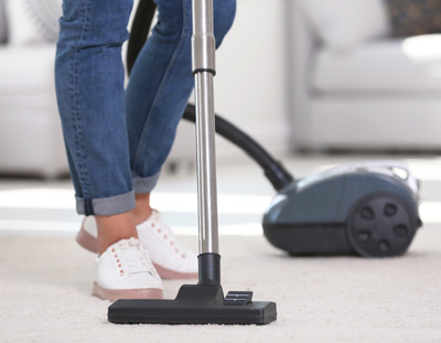 Maid service vacuuming carpet